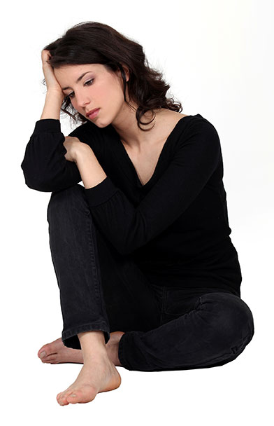 Depressed woman sitting on the ground.